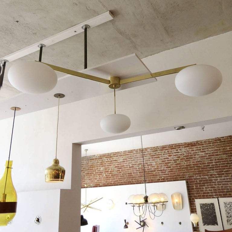 Stunning large-scale three-arm flush mount fixture by Gallery L7, in brass-plated steel and three matte opaline glass globes.