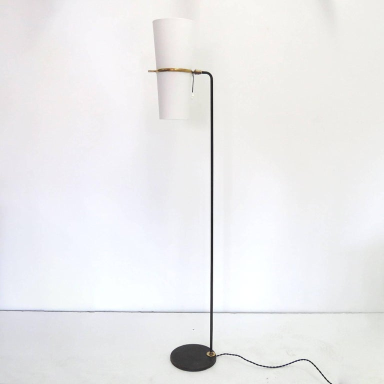 Elegant 1950s floor lamp by the French company Maison Lunel with a white silk double rotary shade, a round blackened steel base, post and brass details. The shades are newly mounted onto the original frames. The light is fully adjustable due to a
