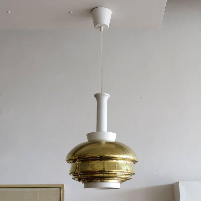 Wonderful pendant light, model A335 by Alvar Aalto, in brass and white enameled metal, with original metal canopy and white bottom rim, early example by original manufacture Valaistustyö, Finland, 1952, stamped with manufacture's mark.