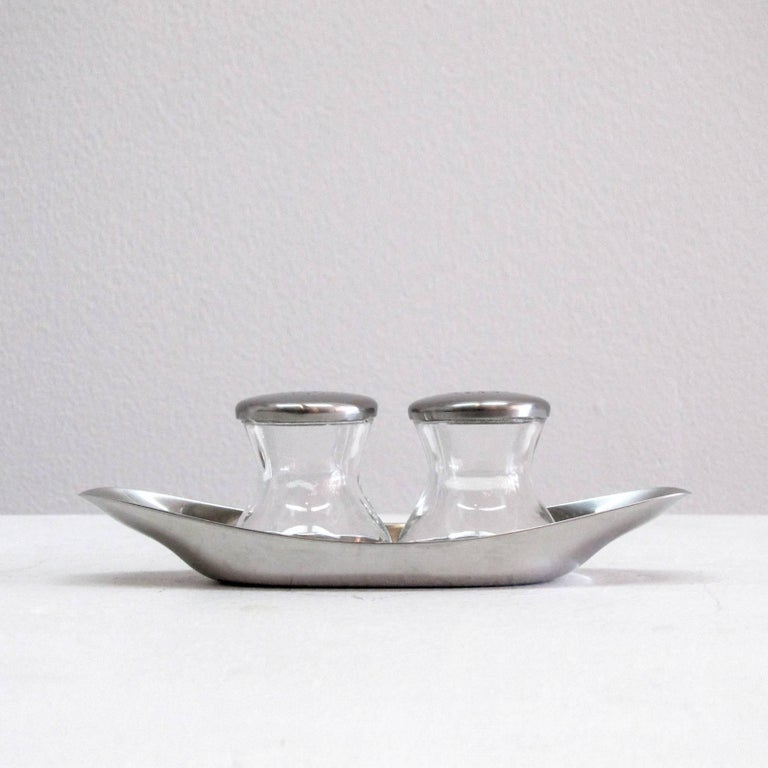 Classic, complete salt and pepper shaker set by Wilhelm Wagenfeld for WMF, WV 505. The set includes two pressed glass shakers with perforated lids and a cromargan (stainless steel derivative) plate or holder, part of the MoMA permanent collection.