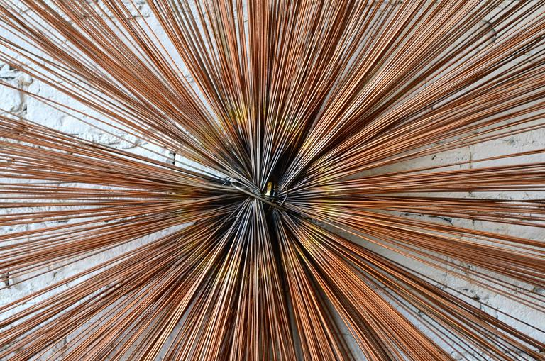 Starburst wall sculpture. Unlike its Curtis Jere starburst counterparts, this piece is comprised of multiple concentric layers of metal spokes. It has a dark bronze patina finish. Outstanding quality.