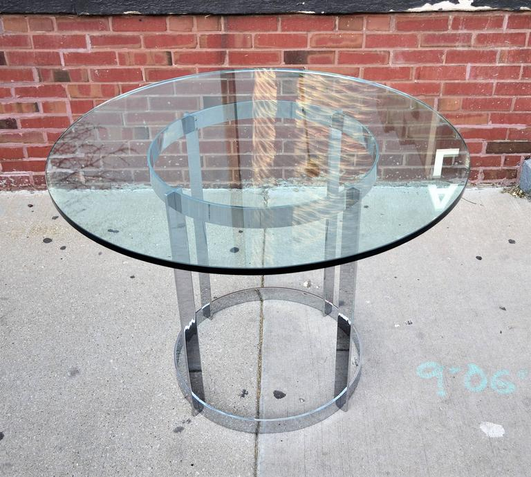 A well made heavy solid chrome Milo Baughman for Thayer Coggin round dining table with a thick glass top. Its modern Minimalist design and versatile size lends itself to multiple uses. Side or end table, center table or even a games table.
