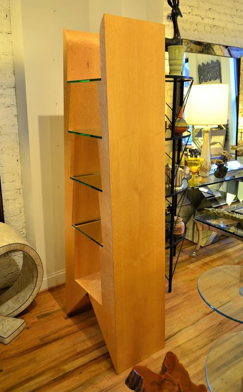 A post modern Memphis style highly sculptural bookshelves. The unit has four glass shelves and is illuminated from the base. A versatile display piece or a freestanding room divider. Reminiscent of Ettore Sottsass's Adesso Pero bookcase from the