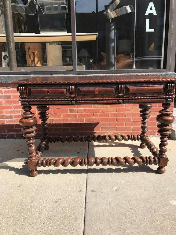Portuguese rosewood 18th Century console table. This Baroque Portuguese Mesa Butte table has large bulbous ring turned legs. Its turned barley twist stretchers have carved opposing spiral turnings. The table has three drawers with keyholes. There is