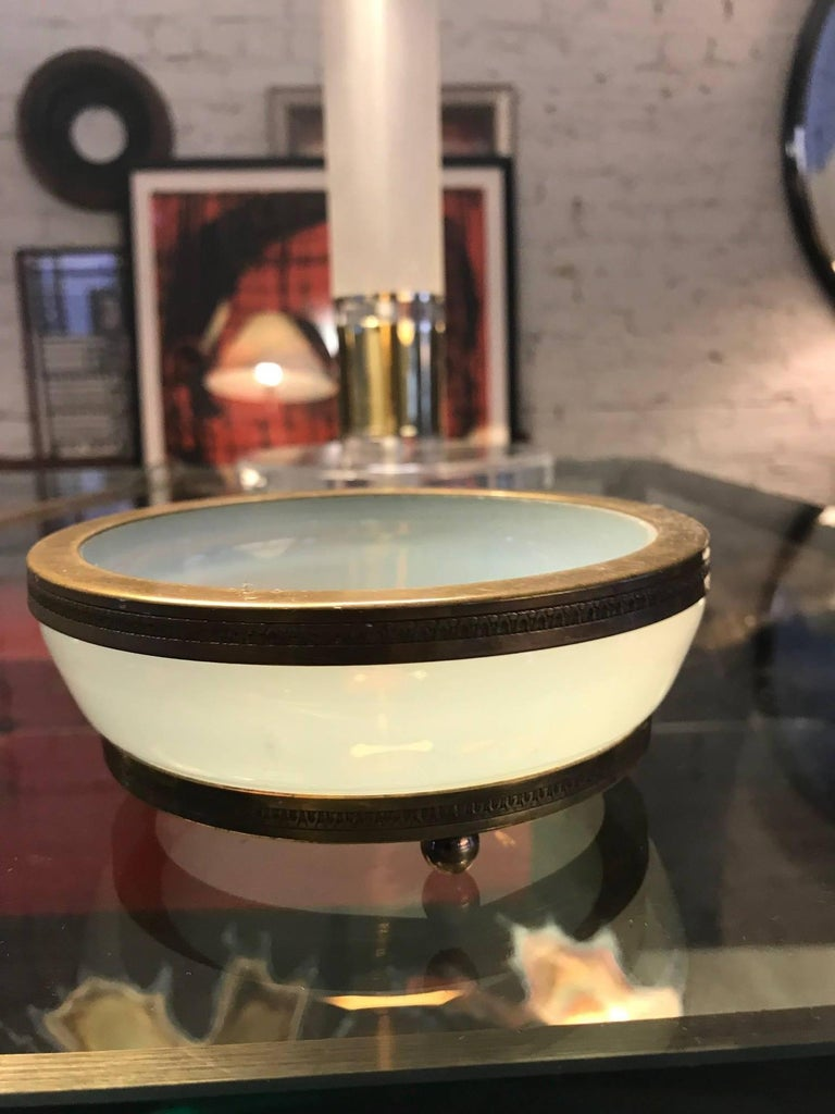 A 19th century French opaline glass bowl vide poche catchall with gilt bronze mounts. The bronze is finely sculpted. The thick glass bowl rests on ball feet. A fine decorative tabletop object.