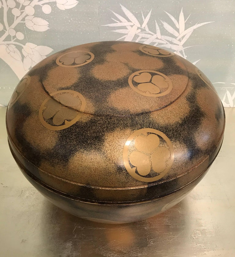 Very large round 19th century Japanese lacquer covered box with pawlonia leaf crests.