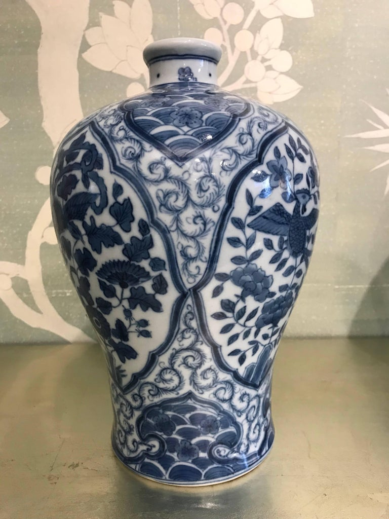 Pair of Korean mid-20th century blue and white vases with reserves of birds, flowers, and wave borders.