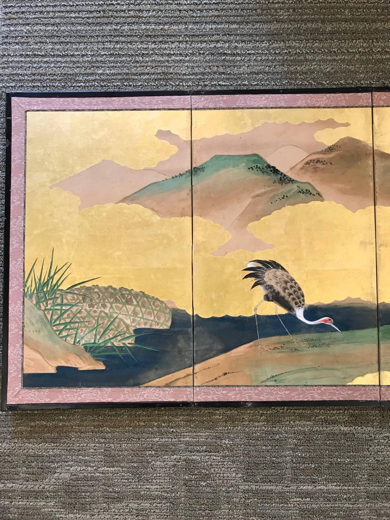 A six fold Japanese screen with pine trees, cranes, and bamboo on a gold leaf background, early 20th century.