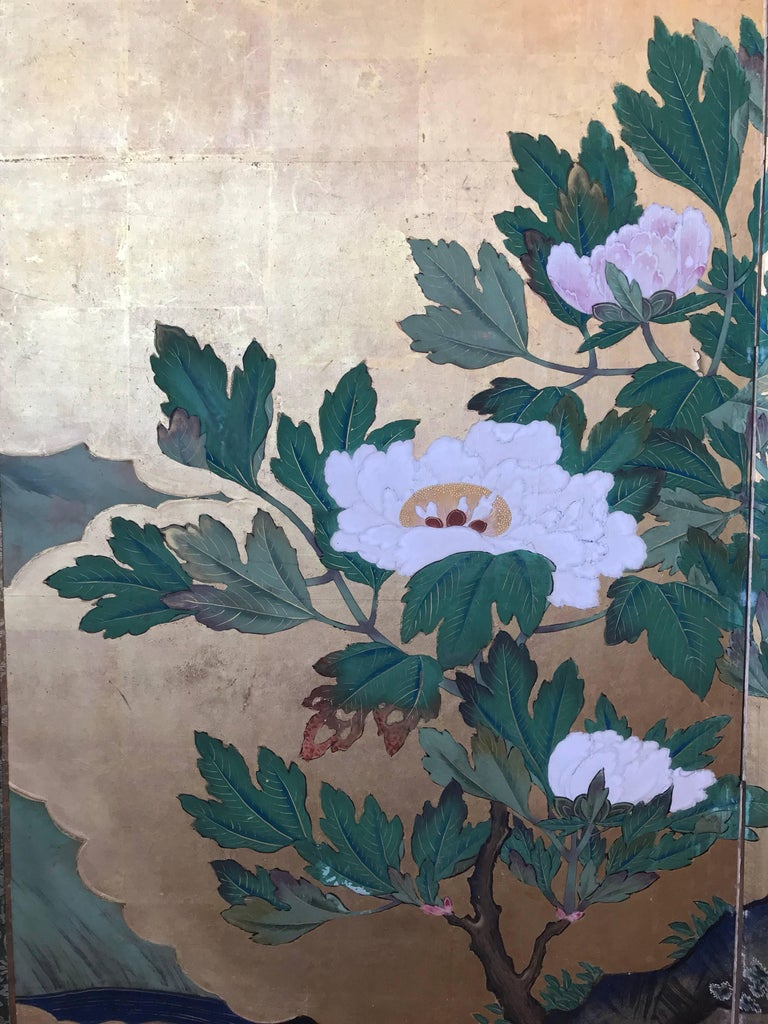 A Japanese four-panel screen with large scale peony blossoms, bamboo, and cherry blossoms on a gold leaf background.