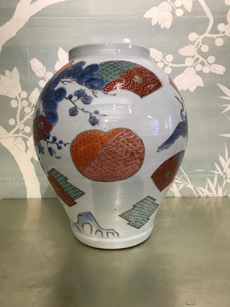 A large early 20th century Japanese Arita jar with beautifully detailed design of pine tree, cranes in flight, and scattered fans.