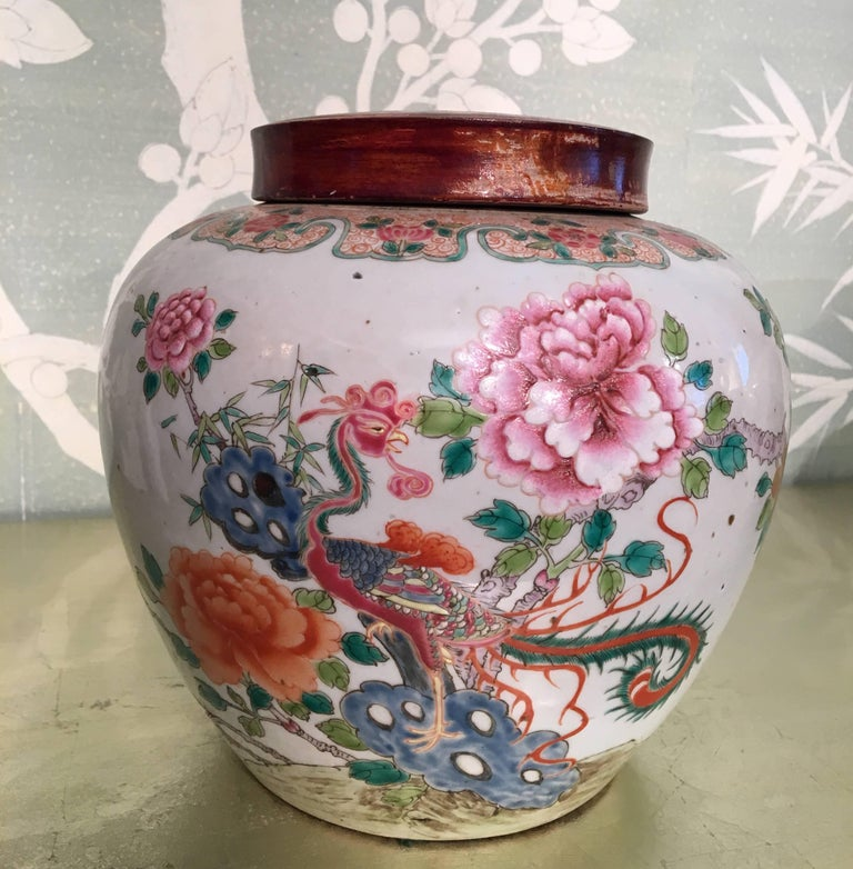 A pair of late 19th century Chinese famille rose ginger jars with design of phoenix and peonies. Jars with wooden lids.