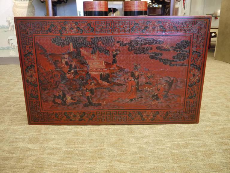 An interesting low Chinese antique lacquer table.  With incised and detailed landscape and figure design and intricate borders.  Unusual legs of geometric form.