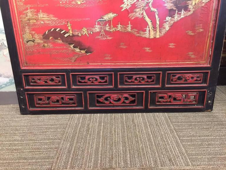 A beautiful, large scale Chinese panel, hand painted in gilt and darker tones on a red lacquer background, and framed with an open work border at the top and base.  Design is of figures and pavilions among water and mountains. There is openwork