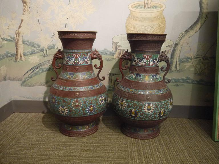 Turn of the 20th century pair of metal vases with inlaid enamel design in bands of bold patterns, with lion handles.