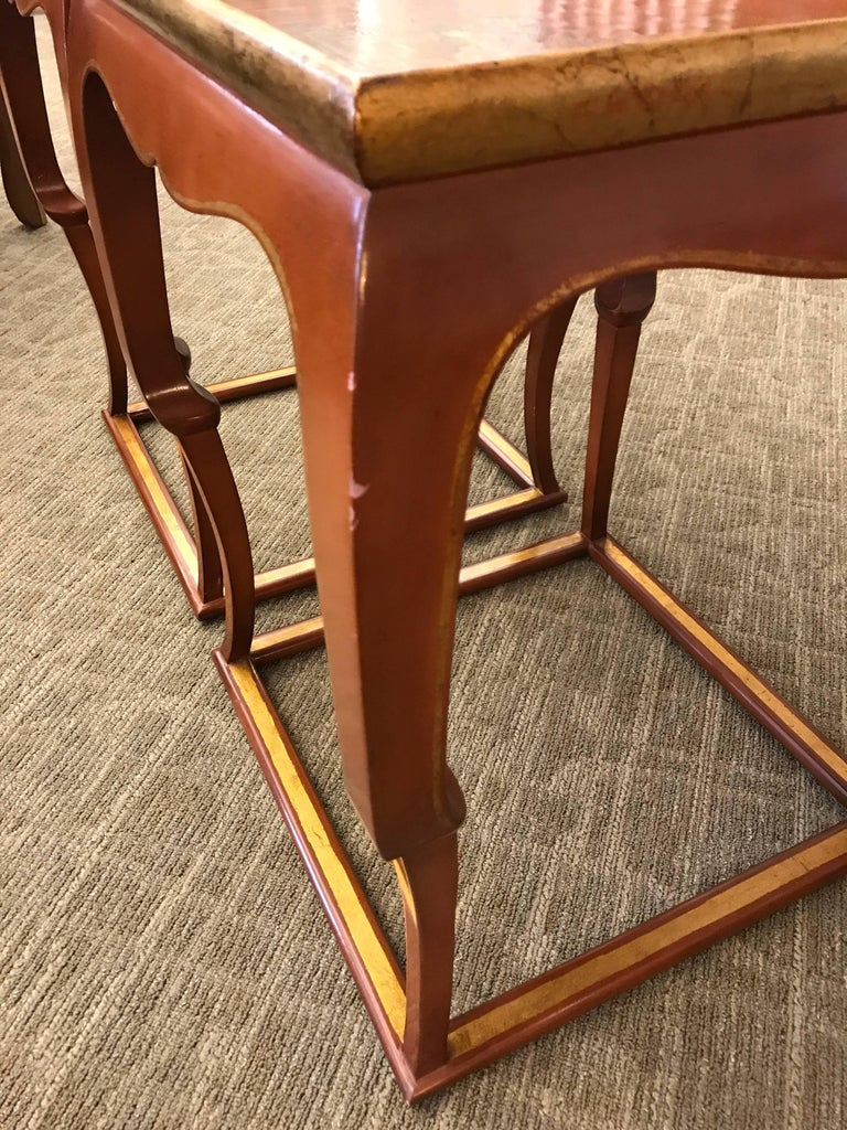 A graceful pair of tables.  With intentionally crackled lacquer tops, in cognac lacquer color, with gilt design at corners.
