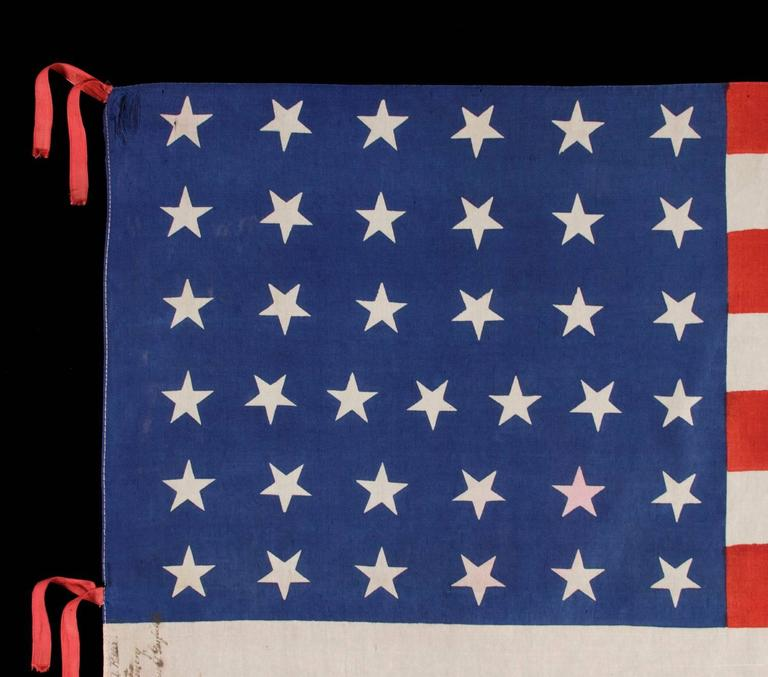 37 STARS ON A LARGE SCALE SILK PARADE FLAG WITH HAND-INSCRIBED MOURNING NOTATION REGARDING THE 1880 DEATH OF PRESIDENT JAMES GARFIELD AND ITS STARS ARRANGED IN A