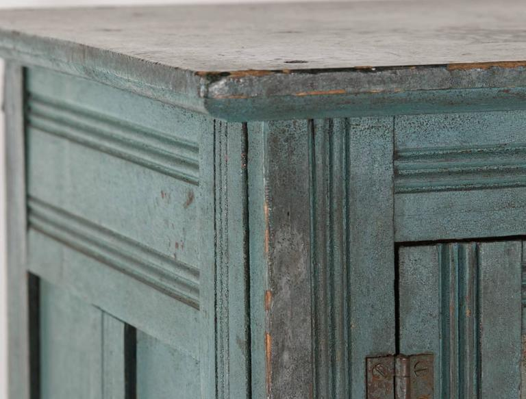 Four-tin, two-door pie safe with paneled sides and reeded decoration throughout on the stiles and legs. The lofty, narrow form is particularly attractive, but the cupboard's best feature is its dry, blue painted surface with wonderful patina. There