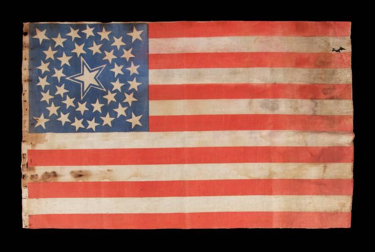 36 stars in a medallion configuration on a parade flag with a huge, haloed center star; a rare example, large in scale, Civil War era, Nevada statehood, 1864-1867.