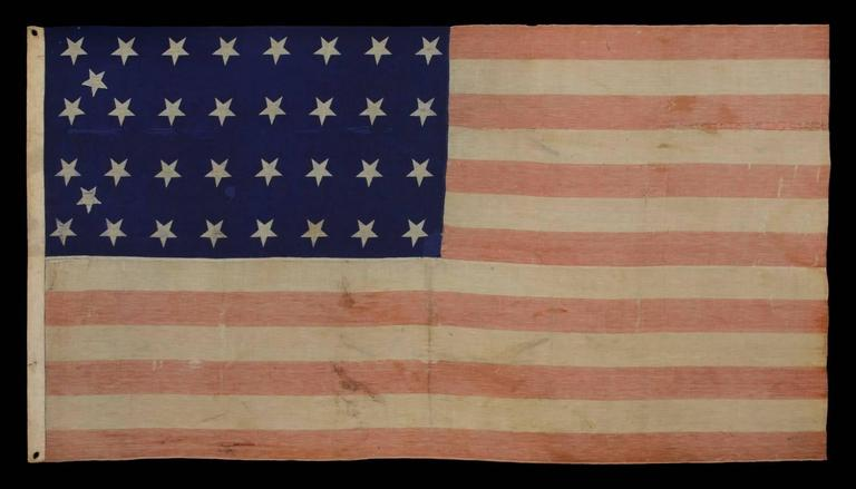 34 stars, Civil War period (1861-63), an unusual example with woven stripes and press-dyed stars, possibly made in New York by the Annin Company: 34 star flag, of the Civil War period, made of a press-dyed canton and woven stripes. This uncommon