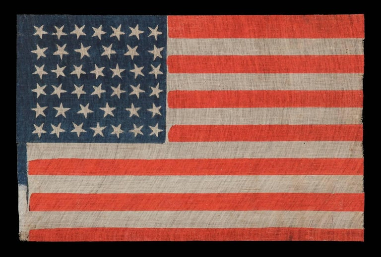 40 STARS, AN EXTREMELY SCARCE EXAMPLE AND AN UNOFFICIAL STAR COUNT, ACCURATE FOR JUST SIX DAYS, SOUTH DAKOTA STATEHOOD, 1889:   40 star American national parade flag, printed on coarse, glazed cotton. During the 3rd quarter of the 19th century, it
