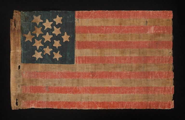 13 STARS ARRANGED IN 6-POINTED GREAT STAR / STAR OF DAVID PATTERN, A RARE AND PARTICULARLY EARLY EXAMPLE AMONG PARADE FLAGS IN THIS STAR COUNT, PROBABLY MADE FOR POLITICAL CAMPAIGNING, CA 1848-1860:  Printed on coarse, glazed cotton, this 13 star