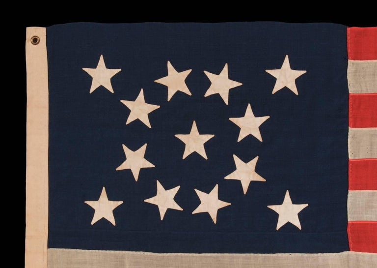 13 HAND-SEWN STARS IN A BEAUTIFUL MEDALLION CONFIGURATION ON A SMALL SCALE ANTIQUE AMERICAN FLAG OF THE 1876 CENTENNIAL ERA:   13 star American national flag, made around the time of the 1876 centennial of American independence. The stars are