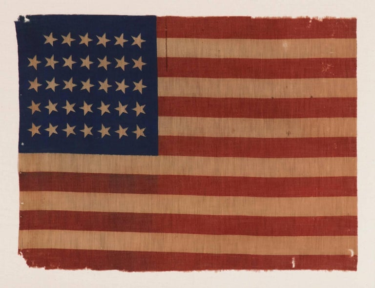 34 STARS, CIVIL WAR PERIOD, PRINTED ON A WOOL BLENDED FABRIC, RARE NOTCHED DESIGN WITH TILTED STARS, POSSIBLY A UNION ARMY CAMP COLORS:  34 star American national flag, printed on a wool and cotton blend. The star configuration, which leaves a