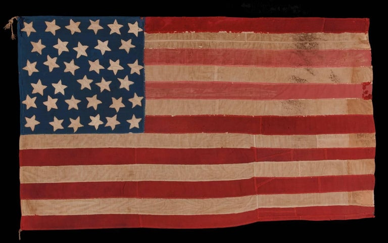 34 star, hand-sewn, homemade, antique American flag of the civil war period, made of a combination of salvaged fabrics, including mens shirting, 1861-1863, opening years of the war, reflects the addition of Kansas :