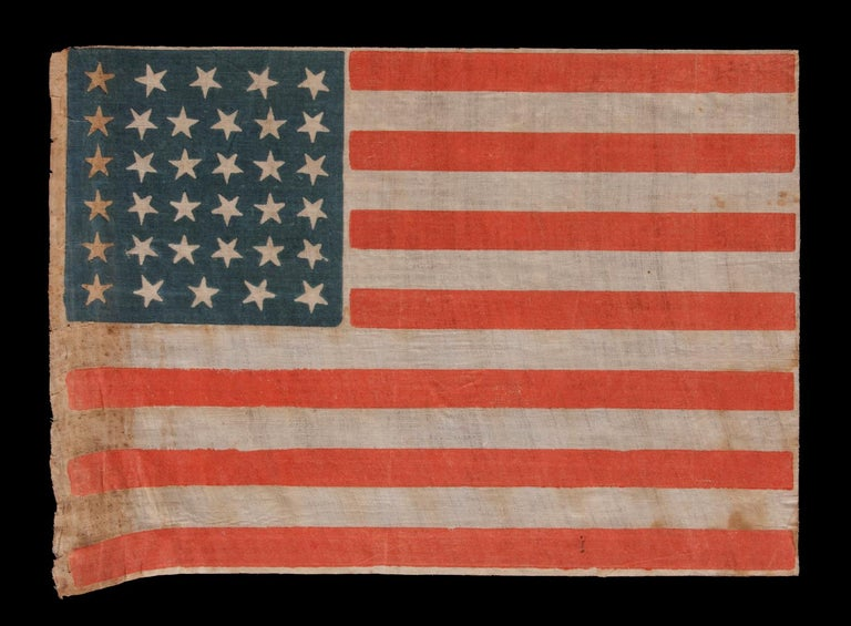 34 STARS, WITH SCATTERED POSITIONING, ON AN ANTIQUE AMERICAN PARADE FLAG MADE DURING THE OPENING TWO YEARS OF THE CIVIL WAR, 1861-63, KANSAS STATEHOOD:  34 star American national flag, printed on glazed cotton. Kansas was admitted into the Union as