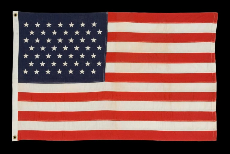 49 embroidered stars on a small scale pieced-and-sewn American flag reflecting the addition of Alaska in 1959, official for just one year, made by Annin in New York city:  49 star American national flag, in a great, small scale among its