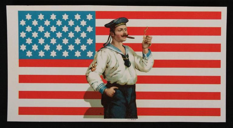 CIGAR BOX LABEL WITH IMAGE OF A 42-STAR AMERICAN FLAG WITH SIX-POINTED STARS AND IT'S BLUE CANTON RESTING ON THE WAR STRIPE, AND AN IMAGE OF A SAILOR LIGHTING A CIGAR, 1889-1920:   This interesting, late 19th or early 20th century (ca 1889-1920)