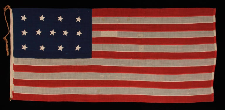 Entirely hand-sewn, 13 star, U.S. navy small boat ensign With A 4-5-4 configuration, Made sometime between 1850 and the opening years of the Civil war (1861-1863):  U.S. Navy small boat ensign with 13 stars arranged in a 4-5-4 pattern of lineal