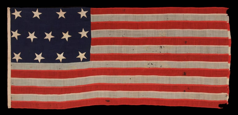Entirely hand-sewn, U.S Navy small boat Ensign of the Civil War period, with 13 stars in A 4-5-4 configuration, in the smallest regulation size recorded by The Navy During This General era:  U.S. Navy small boat ensign with 13 stars arranged in a