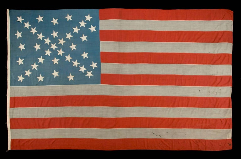 38 Stars in a dynamic starburst cross, one of the most spectacular star configurations in flag collecting, on an antique American flag with possible confederate sympathies, Colorado Statehood, 1876-1889:  38 star American national flag, made