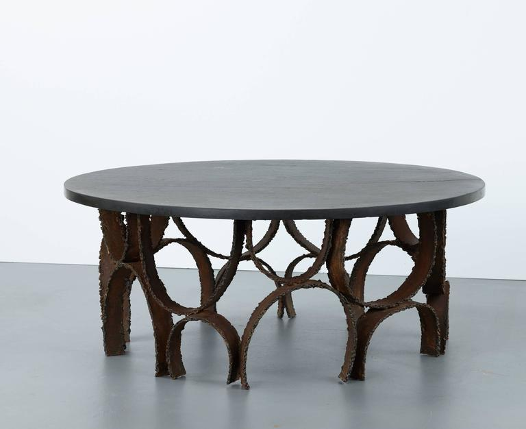 Paul Evans Coffee table with sculpted base and round slate top  Paul Evans Studio USA circa late 1960s  Steel and slate  Studio made and limited production table  Measures: 40 D x 16.5 H in,  101.6 D x 41.9 H cm.