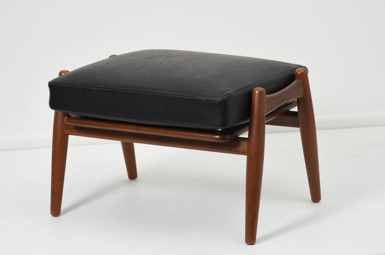 Hans J. Wegner ottoman with black leather cushion  Denmark, 1950s GETAMA  Teak frame with removable leather cushion  Measures: 23.5 W x 19 D x 15 H.  Signed with impressed manufacturer's mark to underside of ottoman GETAMA GEDSTED DENMARK DESIGN