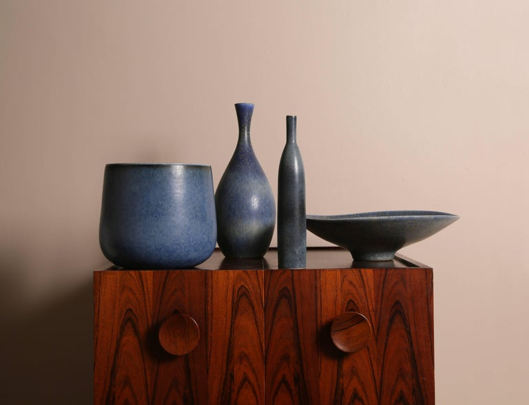 An unusual collection of four ceramic vessels by Carl-Harry Stålhane in blue.  Manufactured by Rörstrand Ab, Sweden, circa 1950s.  Glazed stoneware in various blue, blue-grey and blue-brown tones with a splash of gold pigment in two of the