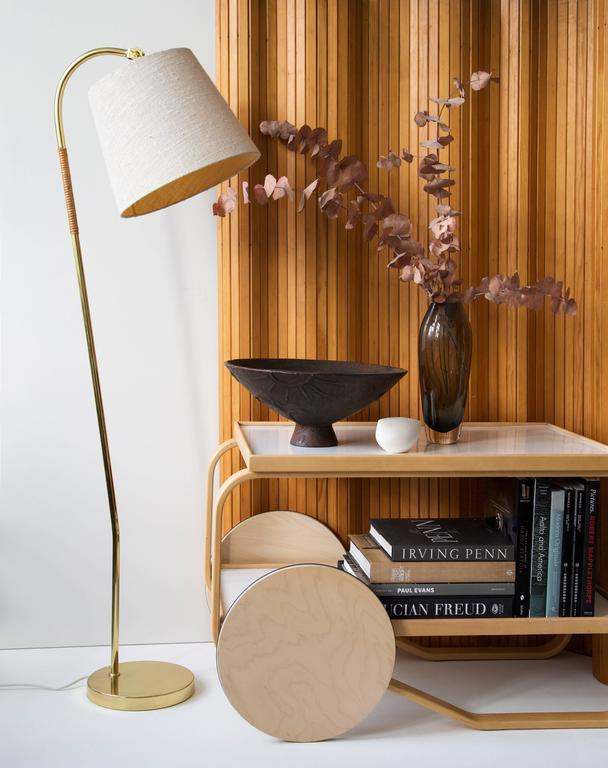 Paavo Tynell floor lamp with cane wrapped stem.  Idman Oy, Finland, early 1950s Brass, cane, fabric shade.  Height 140 cm, width 50 cm, depth 32 cm  Paavo Tynell floor lamp, early 1950s, manufactured by Idman Oy, Finland. Impressed with