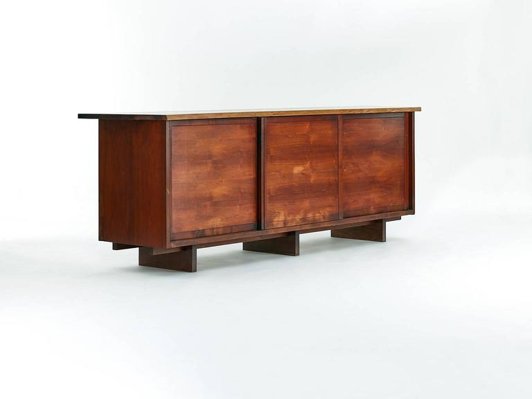 Cabinet by George Nakashima with three sliding doors.  USA, circa 1957.  American black walnut.  Dimention: 95 W x 22 D x 33 H in.  Single-slab top with one free edge. Three sliding doors concealing four adjustable shelves and four