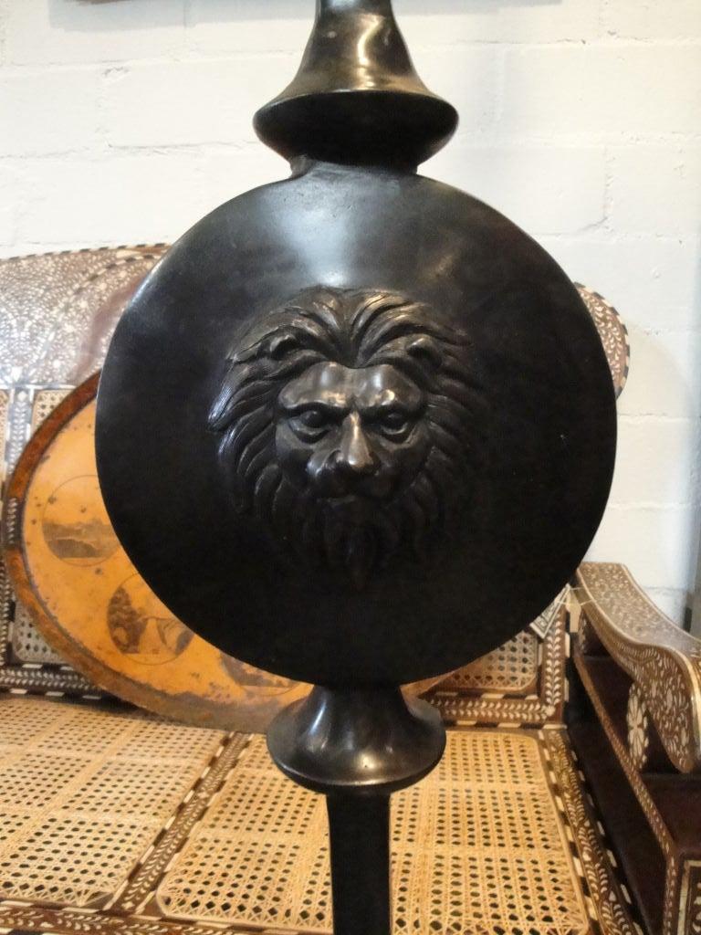Custom bronze floor lamps with lion's head detail.