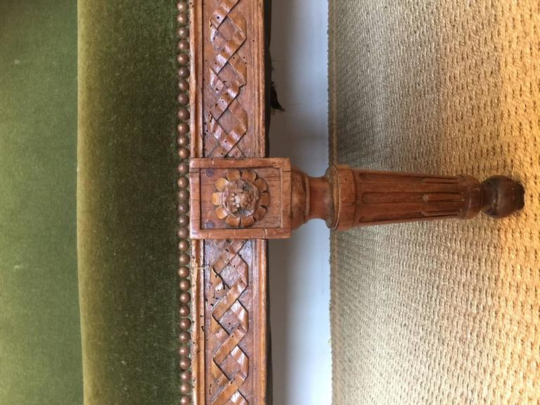 Elegant, green mohair sofa with intricately carved detail and nailhead trim.