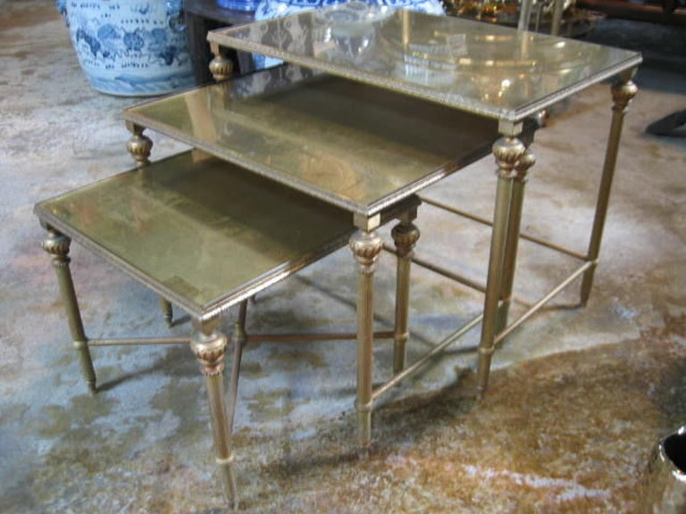 Nesting tables in Neoclassic style with gold-leafed mirrored tops. Antiqued finish with some distressing due to age. Bronze frames and legs have an antiqued patina.