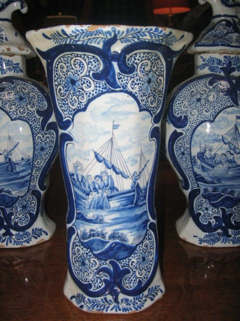 Hand-painted set of blue and white delft porcelain. Three covered vases and two trumpet vases. The lids depict perched birds. The vases depict fishermen in a sailing ship.