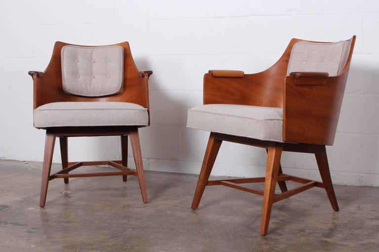 A rare pair of walnut framed lounge chairs with wool upholstery. Designed by Edward Wormley for Dunbar.