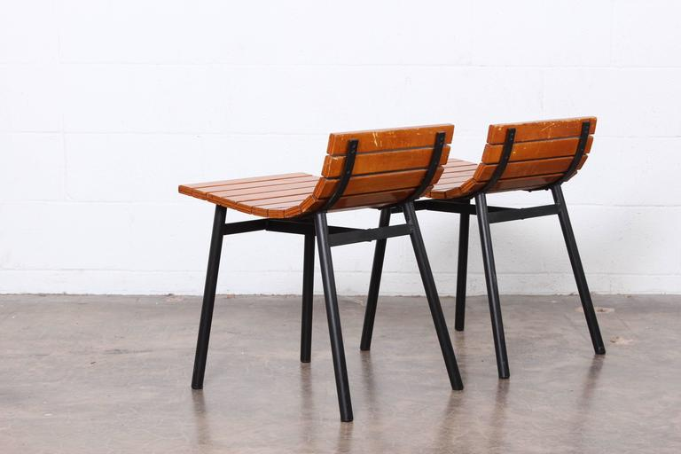 A pair of wooden slat stools with metal bases by Vista of California.