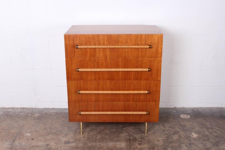 A bleached walnut chest of drawers with cane wrapped handles and brass legs. Designed by T.H. Robsjohn-Gibbings for Widdicomb.