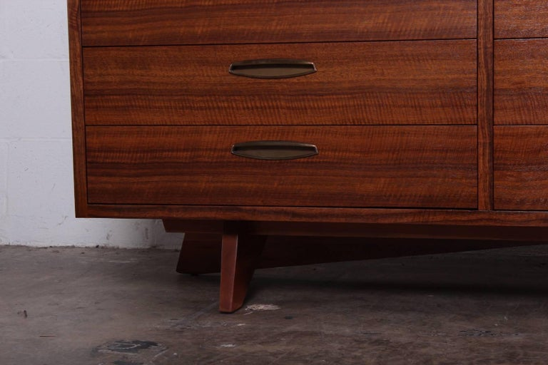 A walnut chest of drawers with brass hardware. Designed by George Nakashima for Widdicomb.