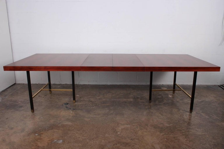 A large rosewood dining table on mahogany base with brass stretchers. Designed by Harvey Probber. Measures: 112