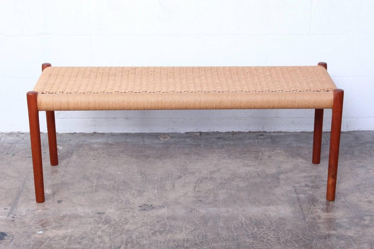 A teak bench with paper cord woven seat. Designed by Niels O. Møller, manufactured by J.L. Møllers Møbelfabrik.