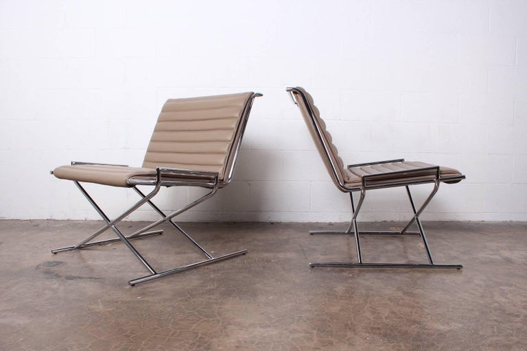 A pair of chrome and leather sled chairs designed by Ward Bennett.